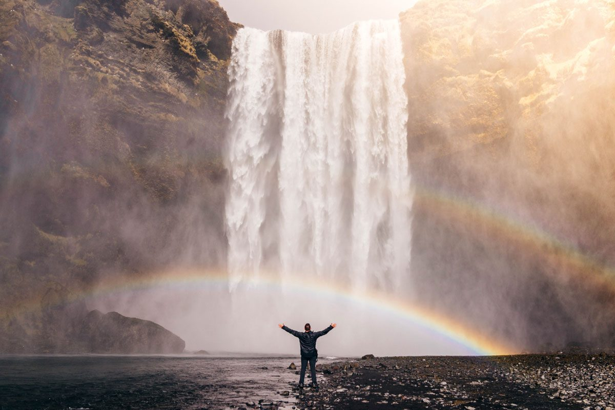 Arms raised in front of waterfall with rainbow