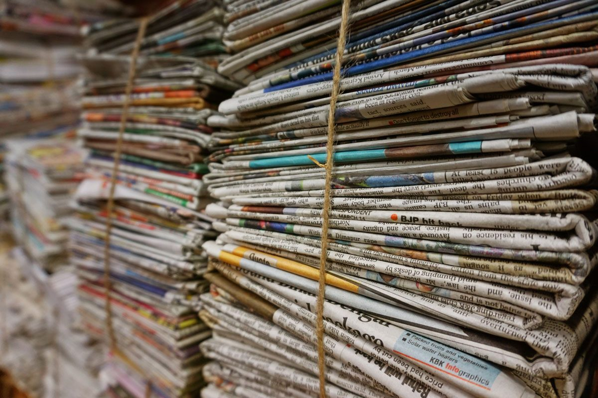 newspapers stacked and tied with string